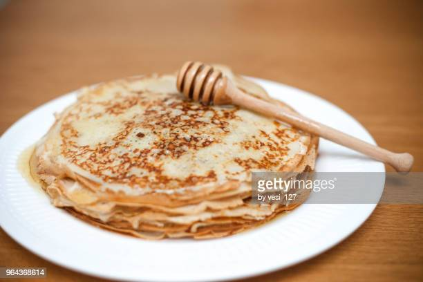 plate of crepes with honey and a honey drizzler - crepes photos et images de collection