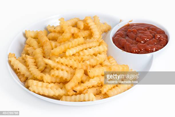 Plate of crispy frech fries with abundant ketchup on the side