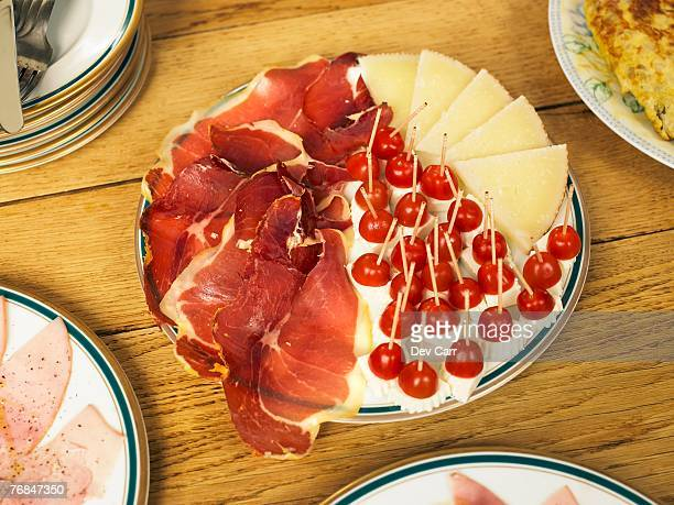 Plate of cured ham and cheese on table, close-up