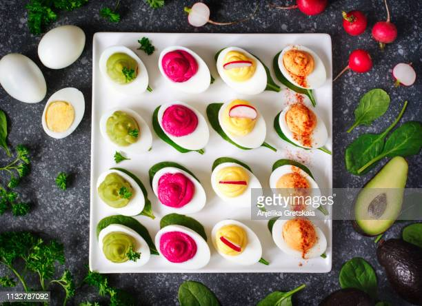 a plate of deviled eggs on dark grey stone background, top view - バイキング形式 ストックフォトと画像
