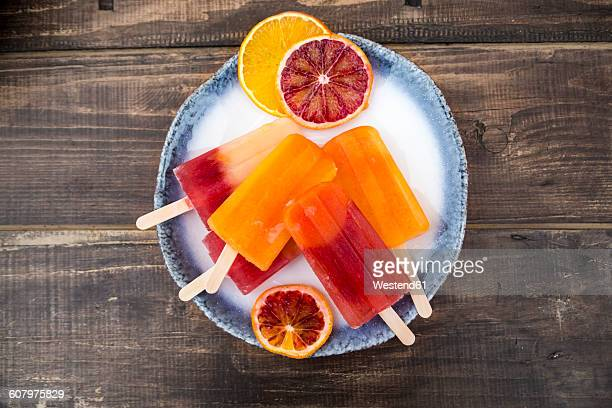Plate of different homemade orange ice lollies and orange slices
