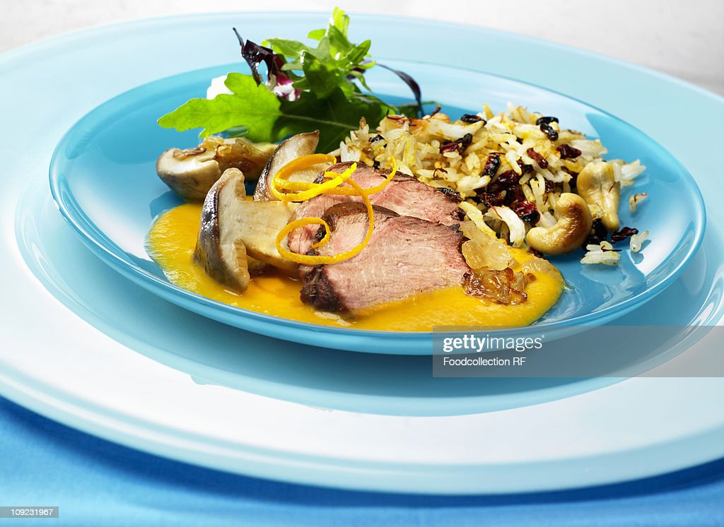 Plate of duck breast with mushrooms and orange sauce : Stock Photo