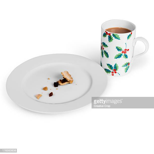 A plate of eaten mince pies and a cup of tea