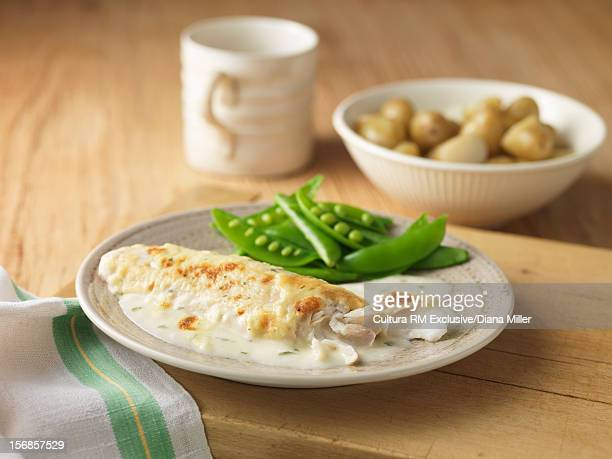 Plate of fish with peas and sauce