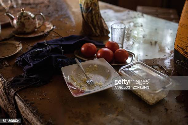 A plate of food sits on a mud splattered table in a house in Mandra northwest of Athens on November 16 after heavy rainfall caused flooding early on...