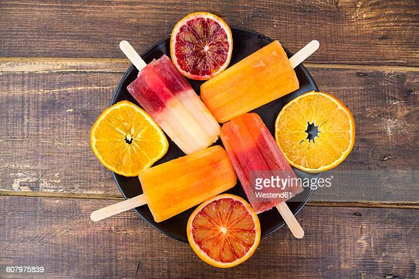 Plate of four different homemade orange ice lollies and four orange slices