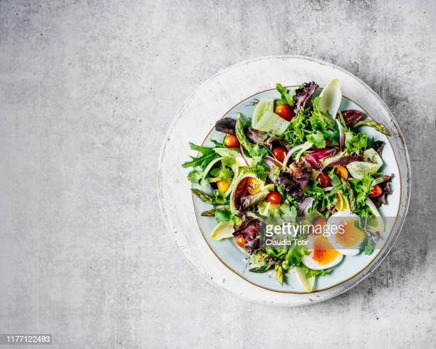 a plate of fresh salad on gray background - salad stock pictures, royalty-free photos & images