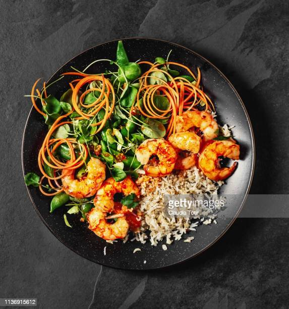 a plate of fresh salad with rice and cooked shrimp on black background - rice food staple stock pictures, royalty-free photos & images