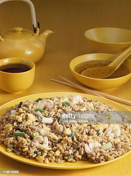 Plate of fried rice with soup bowl and teapot in background