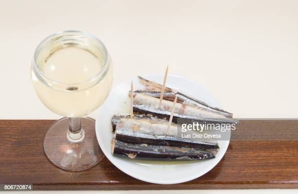 plate of garfish in olive oil and cup white wine