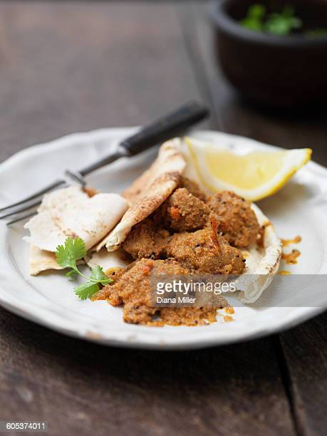 Plate of Goan pork dish with naan bread, lemon slice, coriander and chilli