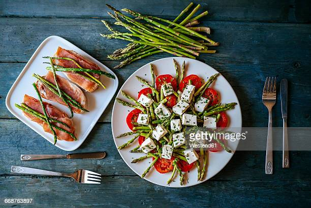 Plate of green asparagus, tomatoes and sheep cheese and plate of bread with cured ham and grilled asparagus