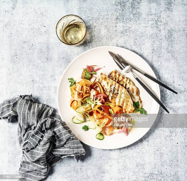 a plate of grilled chicken with carrot salad on gray background - poulet grillé photos et images de collection