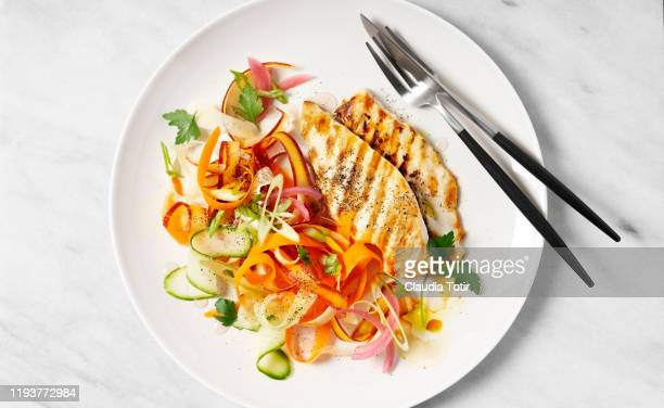 a plate of grilled chicken with carrot salad on white background - poulet grillé photos et images de collection