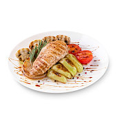 Plate of grilled chicken with vegetables isolated on white background