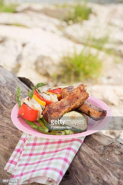 plate of grilled food on tree trunk, close-up - paper plate stock photos and pictures