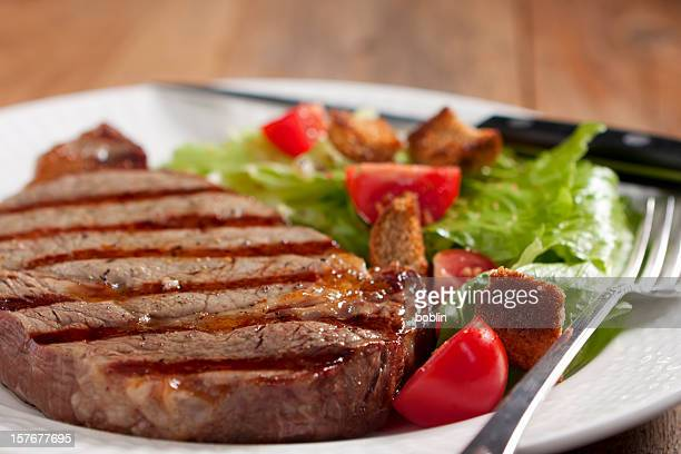 Plate of grilled steak and side salad