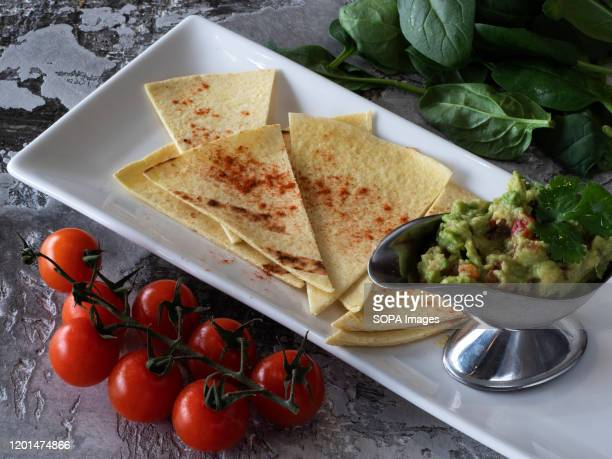 A plate of Guacamole with pita chips seen at Rooster Grill bar and Restaurant in Kiev