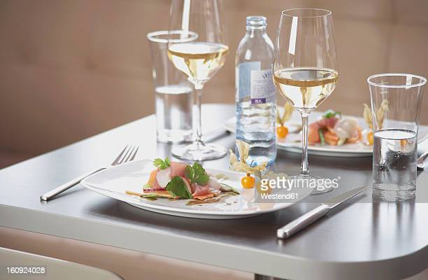 Plate of ham and cantaloupe with wine glass on table