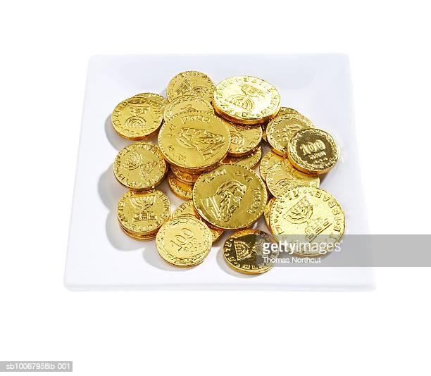 Plate of Hanukah gelt on white background