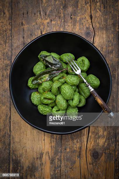 Plate of homemade spinach gnocchi prepared with sage leaves