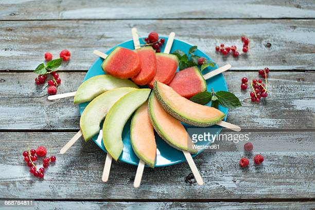 Plate of homemade watermelon ice lollies, slices of Galia and Cantaloupe melon
