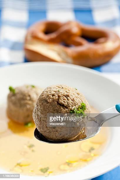 Plate of liver dumplings soup with pretzel, close up