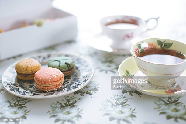 plate of macarons in front of tea cups - tea party stock pictures, royalty-free photos & images