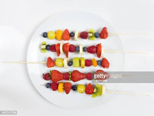 plate of mixed fruits on skewers - bratspieß stock-fotos und bilder