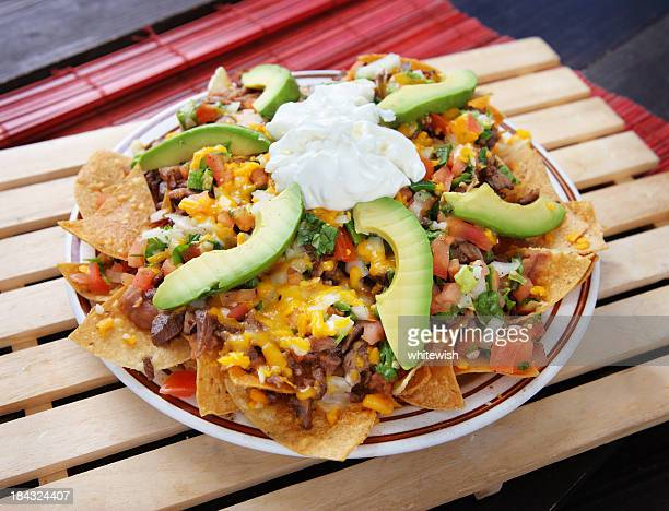 plate of nachos with avocado, cheese and vegetables - dessert topping stock pictures, royalty-free photos & images