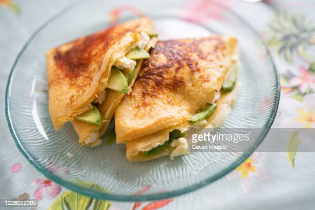 a plate of pancakes with cheese and avocado is on the table with a colorful tablecloth - savory food stock pictures, royalty-free photos & images