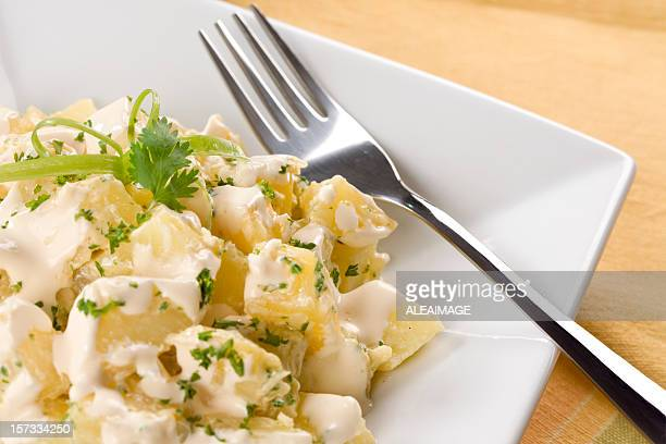 A plate of potato salad with a fork on it