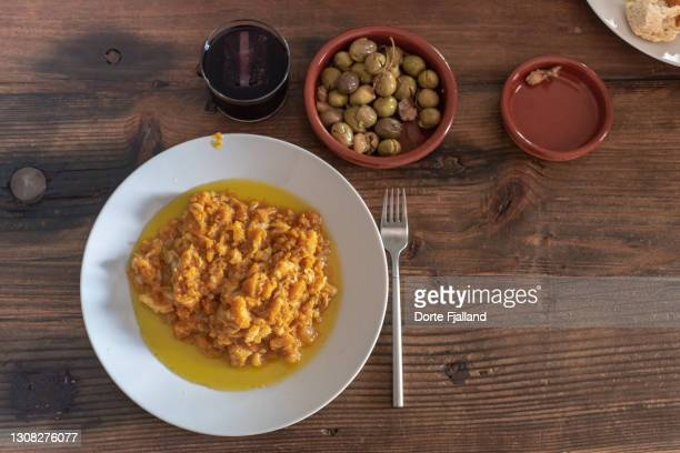 a plate of pumpkin and cod with a glass of red wine and some olives - dorte fjalland fotografías e imágenes de stock