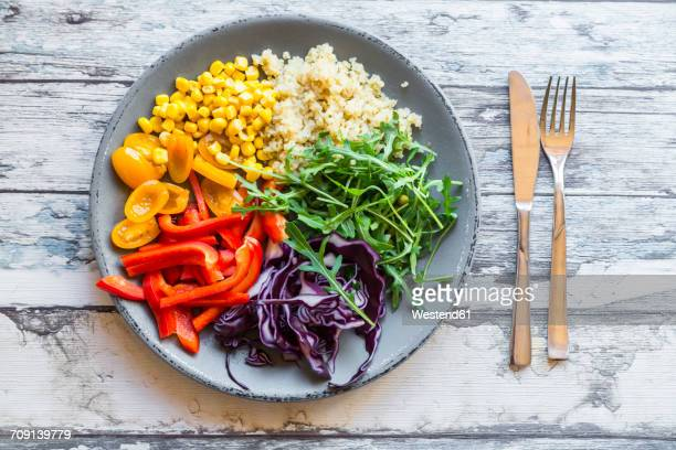 Plate of rainbow salad with bulgur, rocket and different vegetables