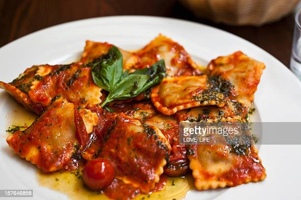 Plate of ravioli In tomato sauce, garnished with basil