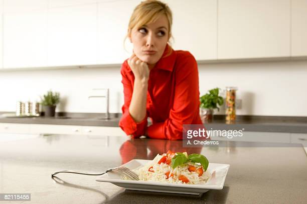 Plate of rice in front of a young woman leaning against a kitchen counter