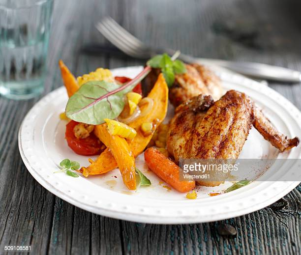 Plate of roasted chicken, cherry tomatoes, carrot, slices of sweet potato and maize on grey wood