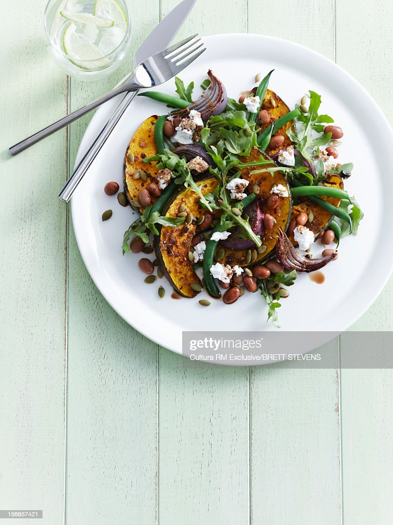 Plate of roasted pumpkin with salad : Stock Photo