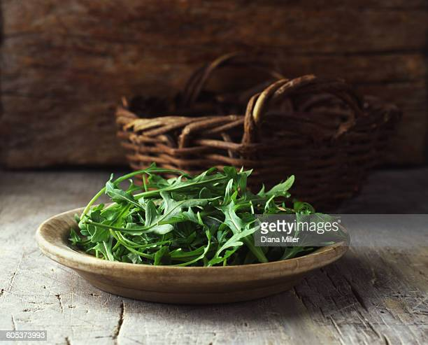 plate of rocket in wooden bowl and wicker basket - arugula stock pictures, royalty-free photos & images