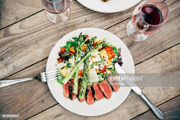 Plate of salad and meat with wine glasses