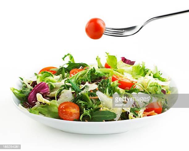Teller mit Salat mit der Gabel und Tomaten
