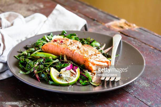 plate of salmon fillet steak roasted with spices served with fresh salad with lime fruit and peppercorns on a wooden table, selective focus. picnic fool. healthy and organic food concept. easter food. - salmon seafood stock pictures, royalty-free photos & images