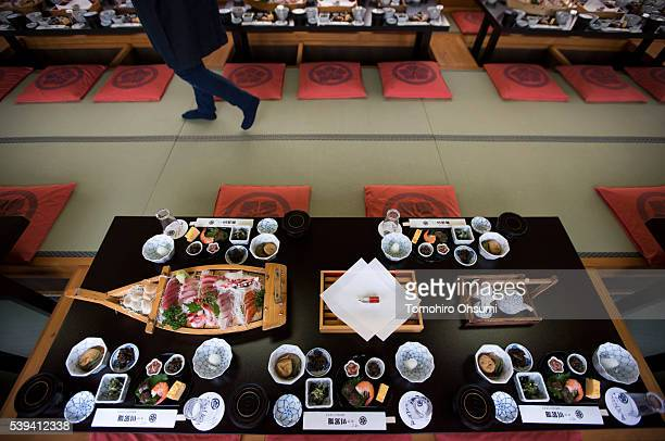 A plate of sashimi slices of raw fish is seen on a table inside a yakatabune or traditional low barge style boat operated by Mikawaya shipping agent...