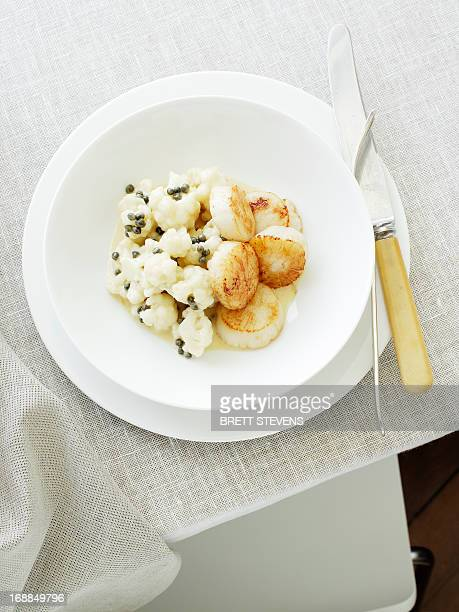 plate of scallops and cauliflower - scallop stock photos and pictures