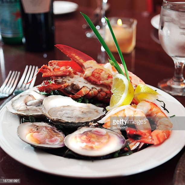 Plate of seafood on table with fork and glass