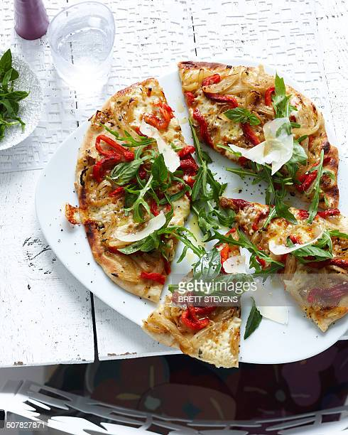plate of sliced wholemeal pizza with herbs, vegetable and parmesan - comida vegetariana fotografías e imágenes de stock