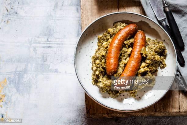 plate of smoked sausages with kale - gerookte worst stockfoto's en -beelden