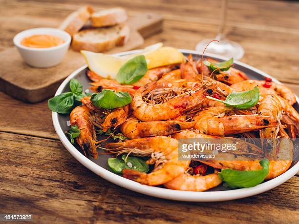 Plate of spicy barbecued prawn on a wooden table