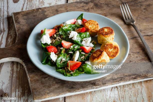 Plate of spinach salad with falafel, goat cheese, strawberries and sunflower seed