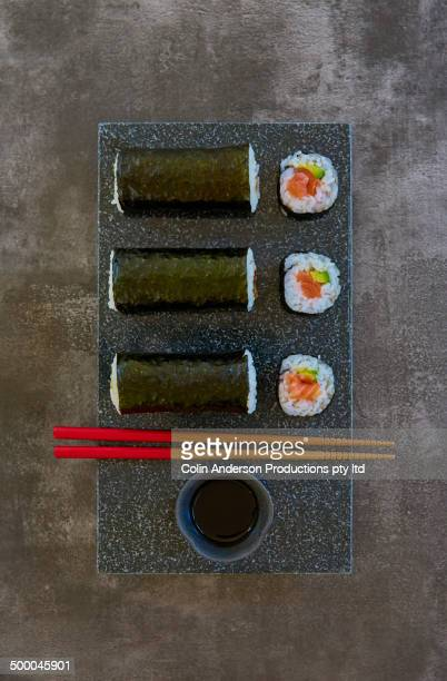 Plate of sushi rolls with chopsticks